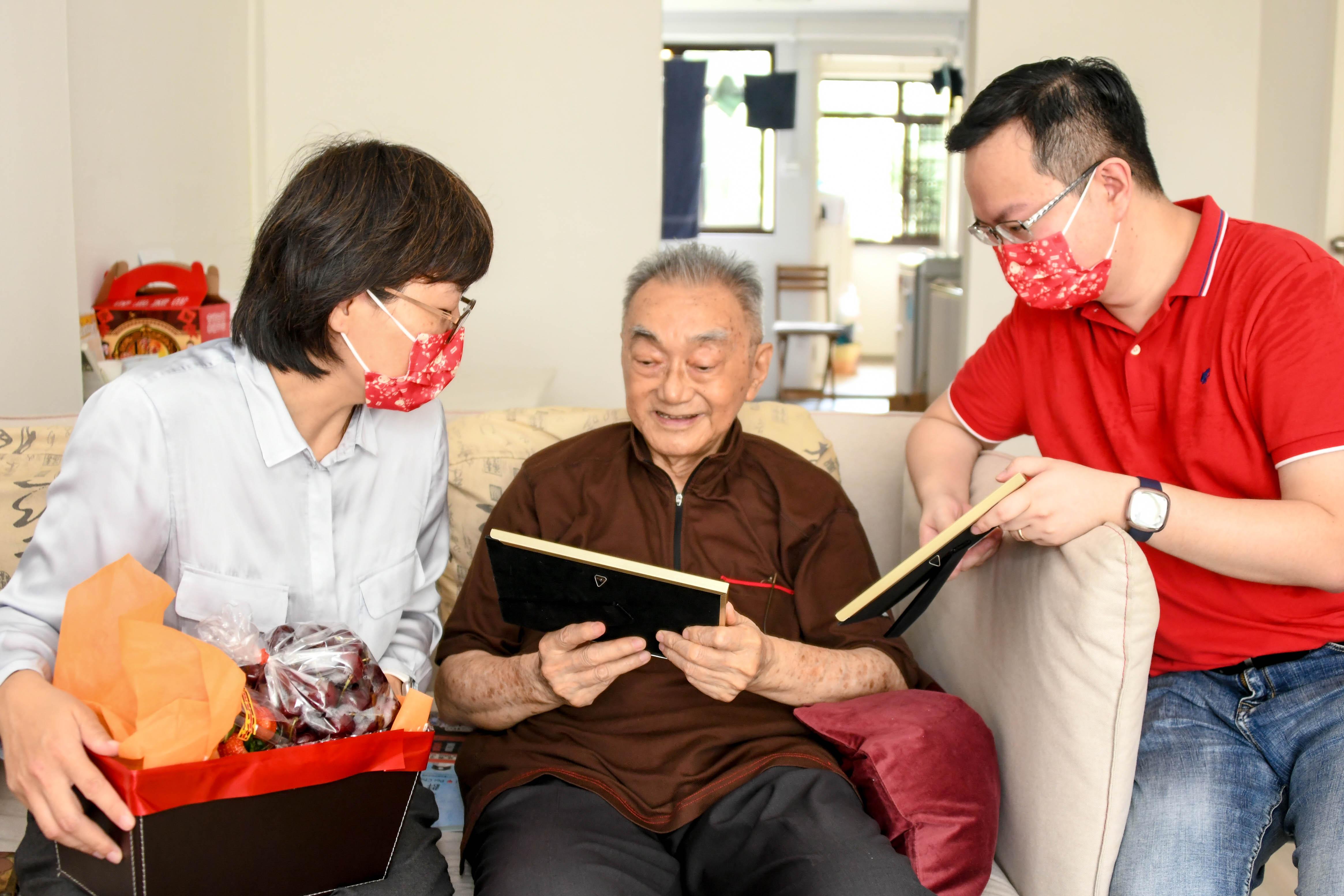 李慧玲(左一)与潘正祥(右一)向老校长介绍由陈聪明校友创作的作品。